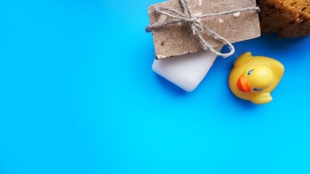 Sapone fatto a mano grigio e bianco e anatra giocattolo giallo su una superficie blu. foto piatta, vista dall'alto
