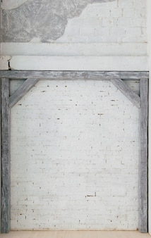 Travi in legno grigie contro un muro di mattoni bianchi.