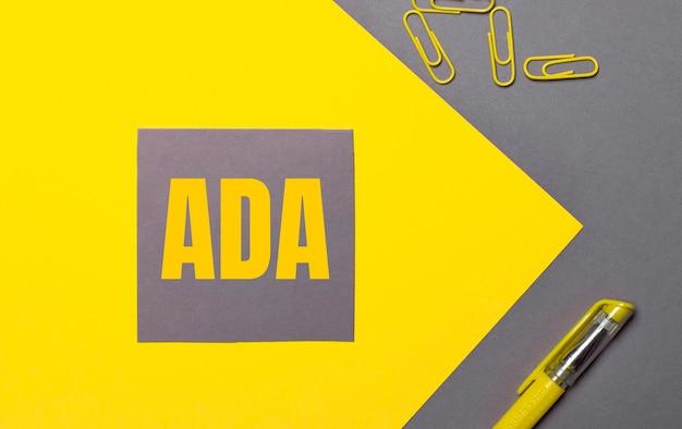 Su uno sfondo grigio e giallo, un adesivo grigio con testo giallo ada americans with disabilities act, graffette gialle e una penna gialla