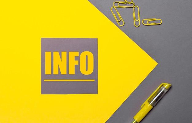 Su una superficie grigia e gialla, un adesivo grigio con testo giallo info, graffette gialle e una penna gialla
