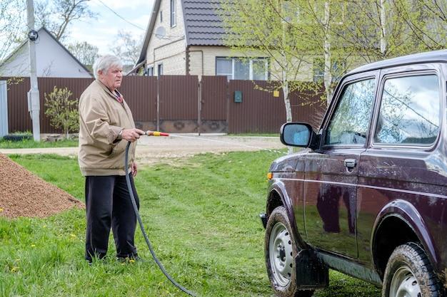 Un uomo anziano dai capelli grigi lava un'auto all'aperto con un tubo da giardino