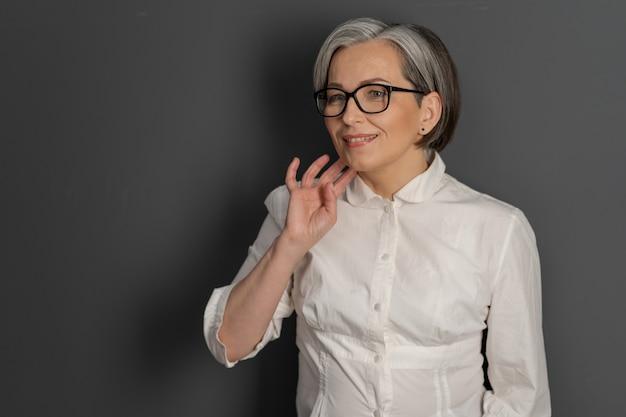 Sorridendo la donna graziosa sorride toccando il mento con la mano civettuola. signora matura astuta in occhiali e camicia bianca sulla parete grigia. spazio testo a sinistra