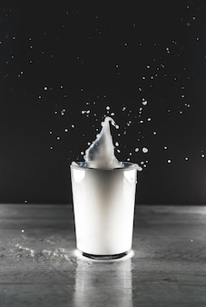 Vista verticale in scala di grigi di una spruzzata di liquido bianco in una tazza di vetro