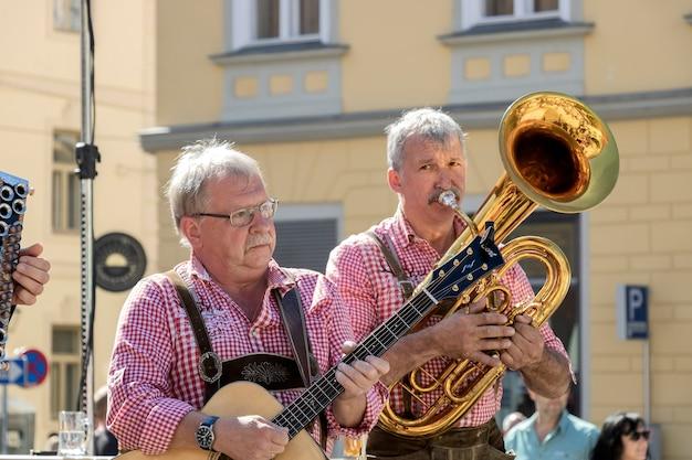 Graz / austria - settembre 2019: festival autunnale annuale della cultura popolare della stiria (aufsteirern). gruppo di uomini in abiti tradizionali luminosi che suonano musica popolare in una piazza cittadina.