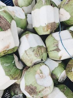 Una grande quantità di noci di cocco verdi. concetto vegetariano, vegano, sano ed estivo