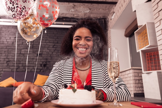 Grande festa di compleanno. allegra donna felice seduta davanti alla torta mentre ti sorride