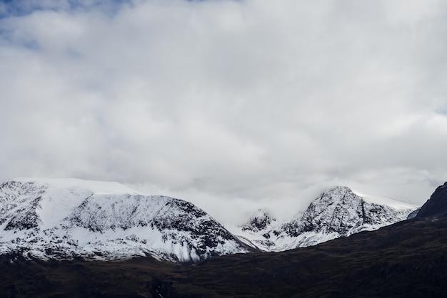 Grandi montagne nere con neve bianca su cime e ghiacciai