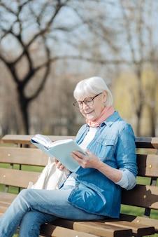 Ottimo libro. donna bionda allegra che legge un libro mentre era seduto sulla panchina