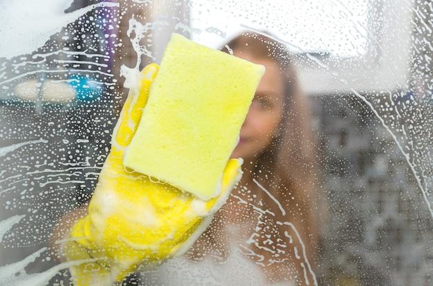 Grande concetto di pulizia domestica, giovane donna bionda che pulisce il vetro dal bagno.