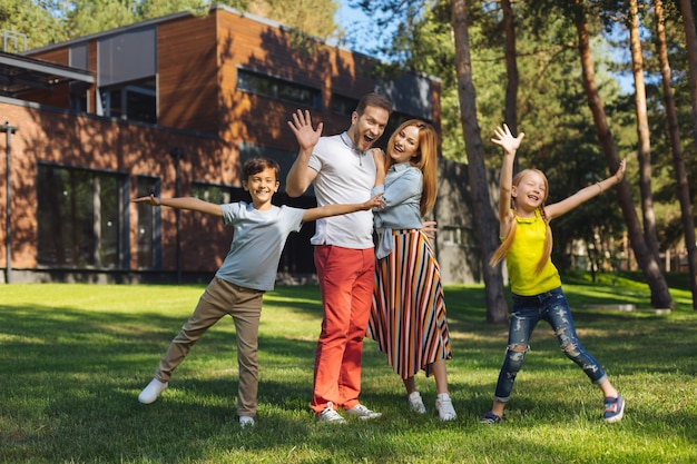 Famiglia fantastica. uomo barbuto esuberante che abbraccia sua moglie e che saluta
