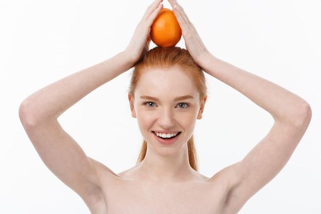 Ottimo cibo per uno stile di vita sano. bella giovane donna senza camicia che tiene pezzo di arancia che sta contro il bianco