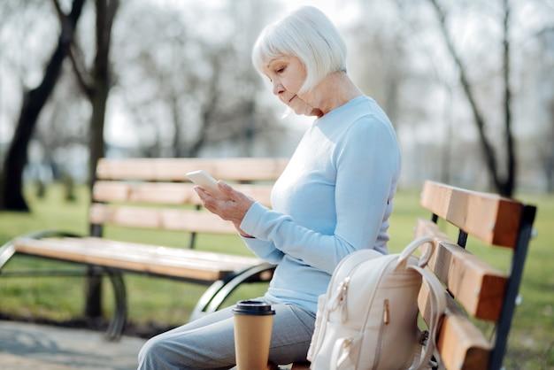 Ottimo gadget. donna invecchiata concentrata che digita sul suo telefono mentre si siede sulla panchina