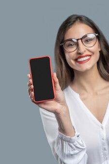 Ottimo gadget. donna dai capelli scuri gioiosa di affari con gli occhiali con lo schermo dello smartphone che mostra tenendolo in mano