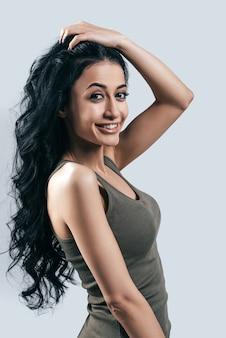 Grande acconciatura! attraente giovane donna in abbigliamento casual che tiene la mano tra i capelli e guarda la telecamera mentre è in piedi su sfondo grigio