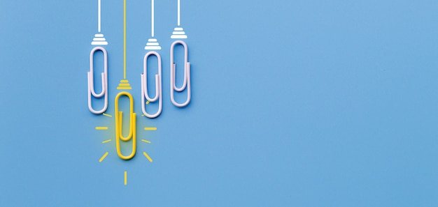 Concetto di grandi idee con la lampadina di creatività di pensiero della graffetta su fondo blu