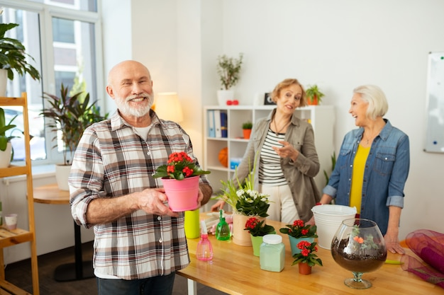 Ottimo umore. uomo anziano allegro che ti sorride mentre tiene in mano un vaso di fiori