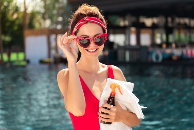 Ottimo umore. donna felice felice che sorride mentre fissa i suoi occhiali da sole alla moda