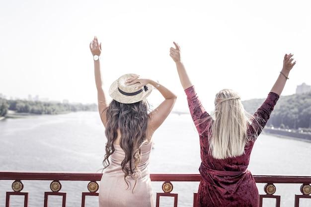 Ottimo umore. felice belle donne che guardano il fiume mentre si godono la loro libertà
