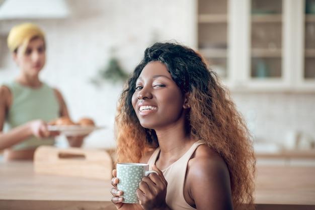 Ottimo umore. giovane donna americana sorridente felice con capelli tinti lunghi con la tazza e la ragazza a distanza in cucina