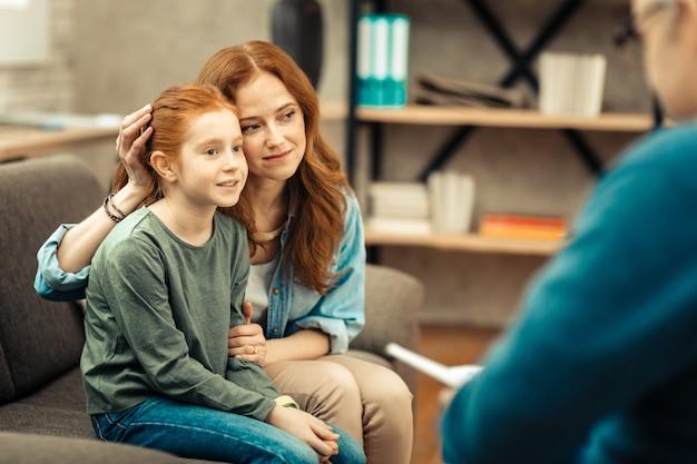 Ottimo umore. bella giovane donna che sorride mentre tocca i capelli di sua figlia