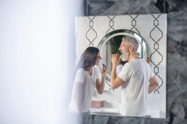 Ottimo umore. profilo di uomo dai capelli grigi e donna dai capelli scuri che lavano i denti di buon umore