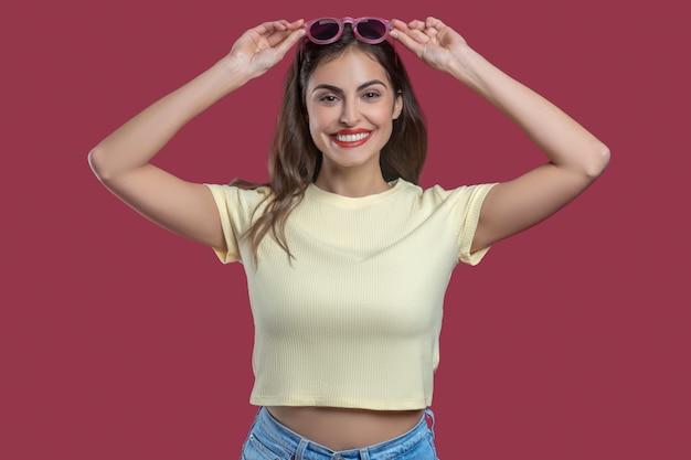 Ottimo umore. sorridente giovane donna graziosa con le mani vicino alla testa tenendo gli occhiali da sole di buon umore