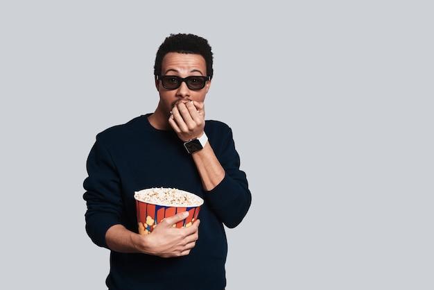 Grande film. bel giovane in abbigliamento casual che guarda la macchina fotografica e mangia popcorn mentre sta in piedi su uno sfondo grigio