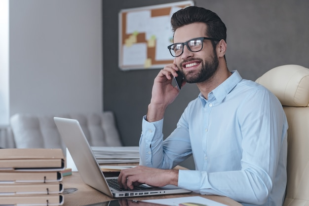 Grandi notizie! bel giovane allegro con gli occhiali che parla al telefono cellulare e guarda lontano con un sorriso mentre è seduto al suo posto di lavoro
