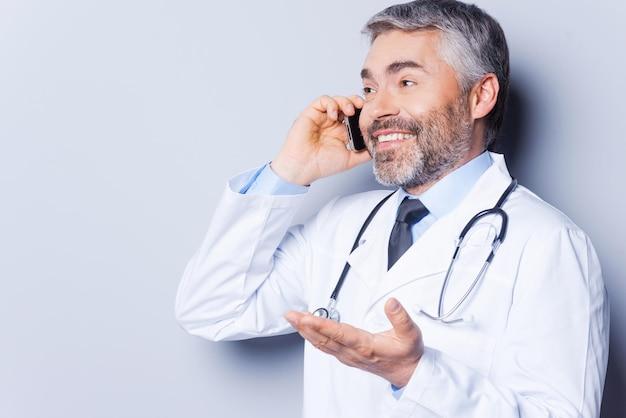 Grandi notizie! medico maturo felice dei capelli grigi che parla sul telefono cellulare e che gesturing mentre stando contro il fondo grigio
