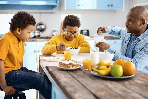 Ottimo passatempo. piacevole giovane padre che parla con i suoi figli durante la colazione mentre si versa un bicchiere di latte