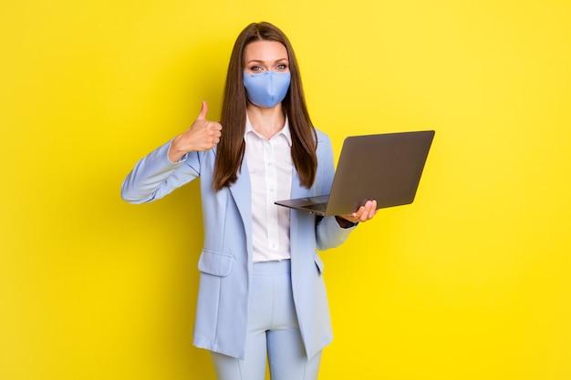 Grande concetto di lavoro decisionale in quarantena a distanza. l'agente di marketing della ragazza usa il laptop mostra il segno del pollice in su indossa la giacca blu giacca sportiva pantaloni pantaloni maschera medica isolato brillante sfondo di colore brillante