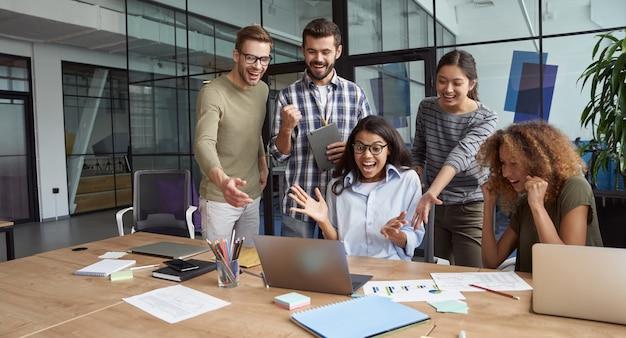 Grandi risultati gruppo di uomini d'affari multiculturali felici che guardano lo schermo del laptop e discutono