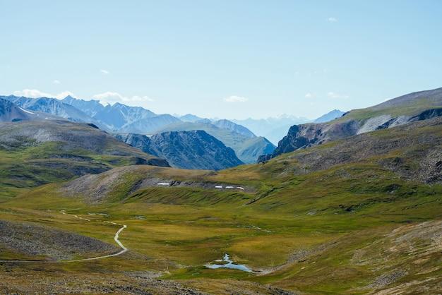 Grandi montagne rocciose e gola profonda dietro una bellissima valle verde con lago negli altopiani.