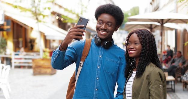 Grande selfie dalla vita in su ritratto della coppia multirazziale innamorata che fa selfie allo smartphone...
