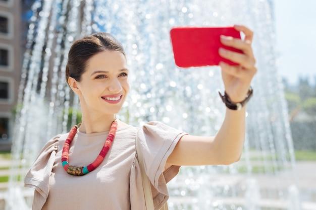 Bel colpo. donna graziosa allegra che sorride mentre prende i selfie vicino alla fontana