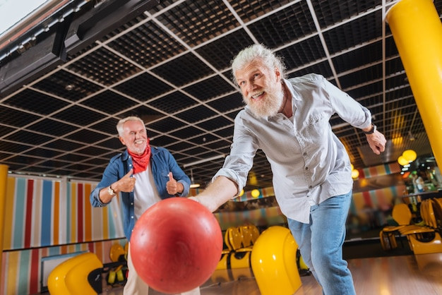 Ottimo tiro. allegro uomo positivo che sorride mentre lancia la palla da bowling