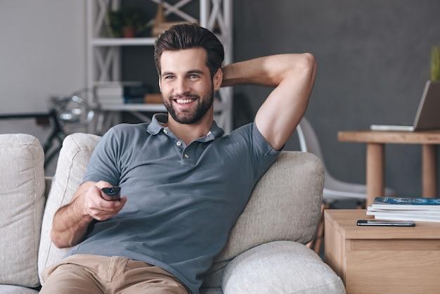 Grande spettacolo televisivo. bel giovane allegro che tiene il telecomando e guarda la tv mentre è seduto sul divano di casa