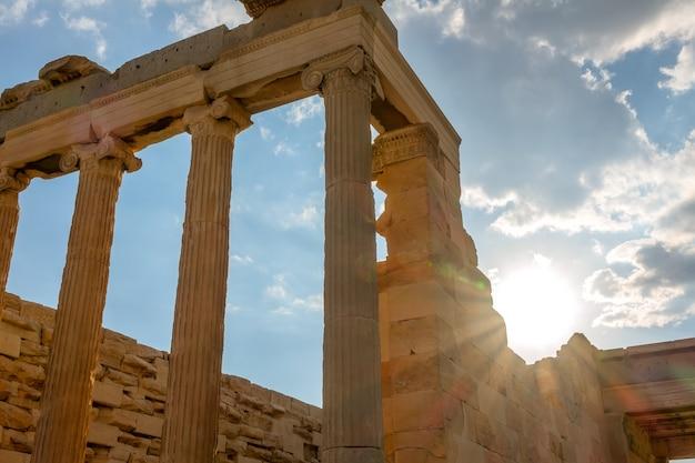 Grecia. atene. parte della facciata di un antico tempio e dei raggi di sole
