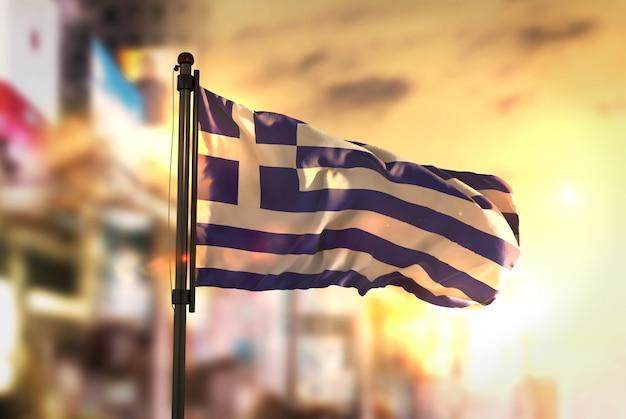 Bandiera della grecia contro la città sfocata di sfondo all'illuminazione di sunrise