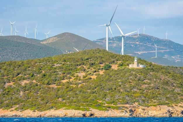 Grecia. costa collinare del golfo di corinto con tempo soleggiato. molti parchi eolici e vecchio edificio del faro