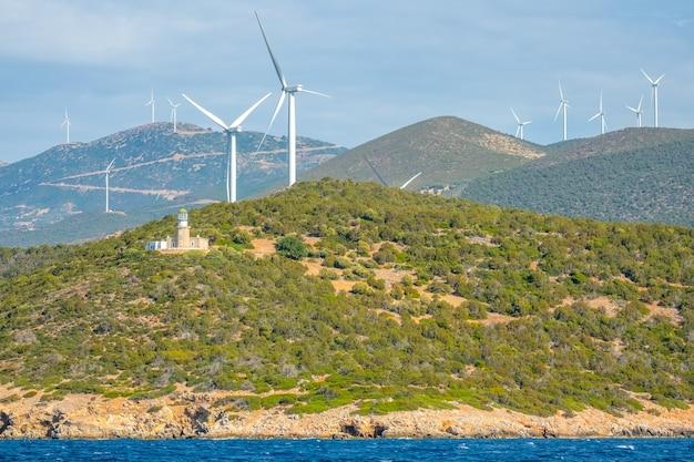Grecia. costa collinare del golfo di corinto con tempo soleggiato. vecchio edificio del faro e molti parchi eolici
