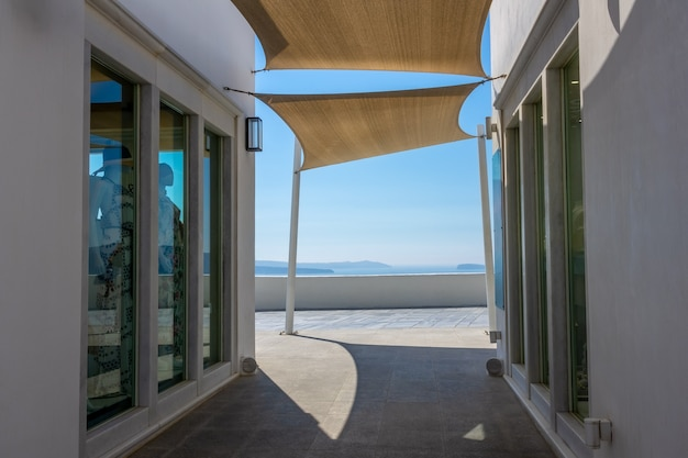 Grecia, santorini. boutique di moda sulla caldera di oia. ombrelloni in tessuto e vista mare