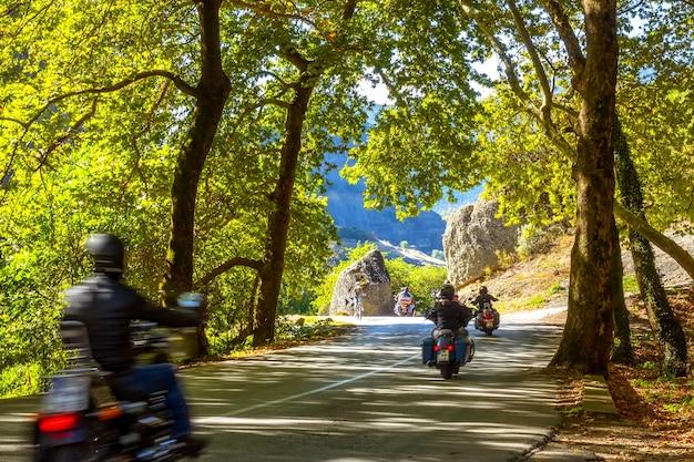 Grecia. giornata di sole estivo all'ombra della foresta su una strada di montagna. diversi motociclisti
