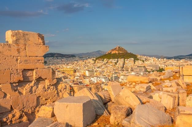 Grecia. tramonto ad atene. rovine di marmo in primo piano. vista da un punto più alto sui tetti della città e sulla collina del licabetto