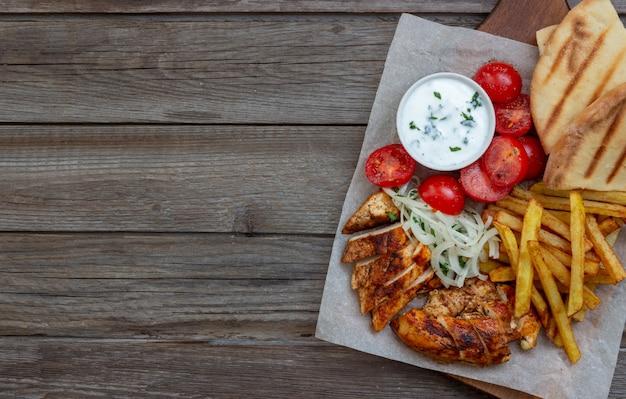 Gyros piatto greco con pollo, patatine fritte, pomodori, cipolle e pita. cucina greca.