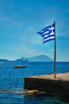 Bandiera greca nel cielo blu sul molo e tradizionale barca da pesca greca nel mar egeo