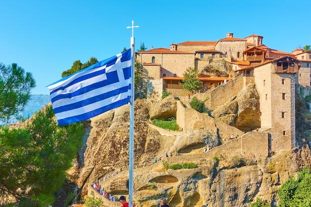 Bandiera greca sul pennone vicino al monastero del grande meteoron a meteora, grecia