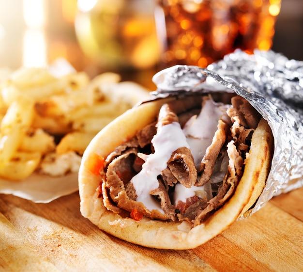 Giroscopi greci con patatine fritte su una tavola di legno