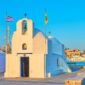 Chiesa greco-ortodossa di agios nikolaos nel porto della città di egina al tramonto, greece