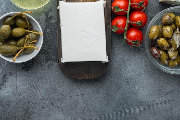 Set di ingredienti per insalata greca, sul tavolo grigio, piatto laici